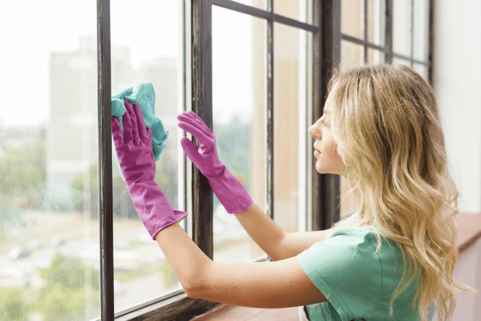 Mujer desinfectando las ventanas para evitar la propagación del covid-19